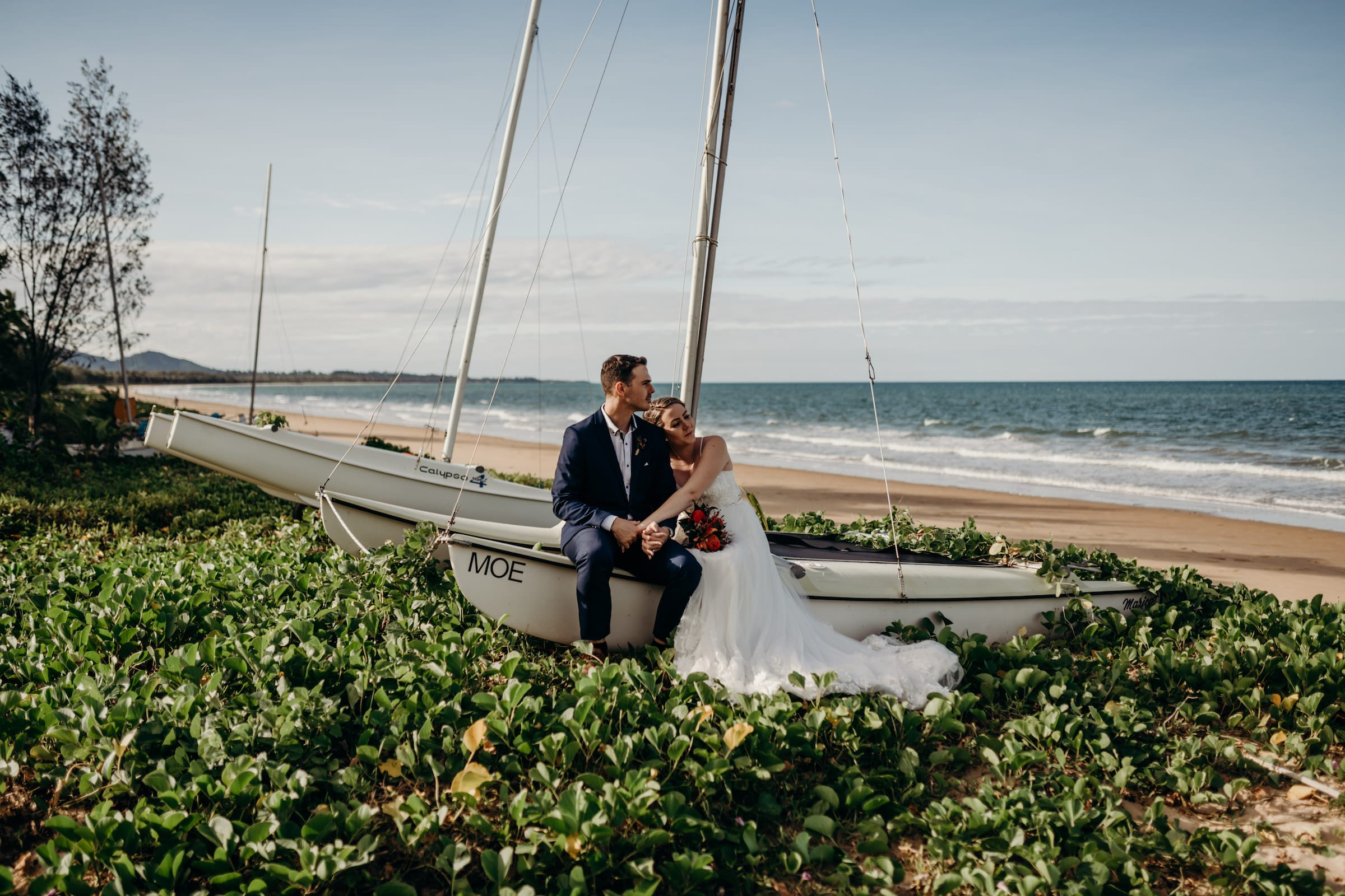 Mission Beach wedding Photographer, couple sitting on a beached boat