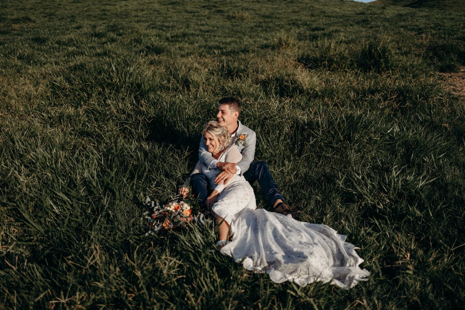 Mission Beach wedding couple laying in the grass